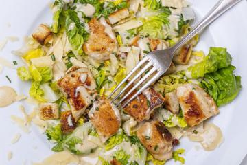 Nahaufnahme einer Gabel auf Cäsarsalat