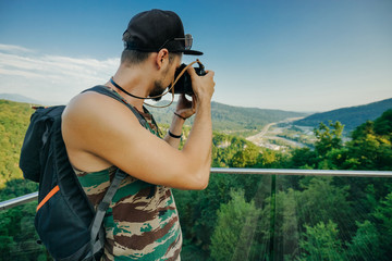 A man photographer in a camouflage T-shirt, a cap and with a backpack holds a camera in his hands and takes a photo of a mountain landscape from a height.