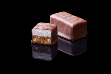Chocolate bar in a cut on a black specular background. Isolated chocolate dessert with caramel filling and nougat. Smooth cut of the chocolate.
