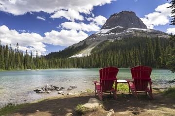 Red Adirondack Chairs at shore of Mountain Lake in Yoho National Park, Canadian Rockies