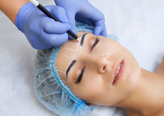 Permanent make-up for eyebrows of beautiful woman with thick brows in beauty salon.  beautician doing  tattooing eyebrow.