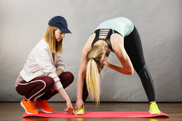 Woman in sportswear stretching legs with trainer