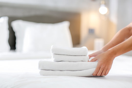 Close-up of hands putting stack of fresh white bath towels on the bed sheet. Room service maid cleaning hotel room.