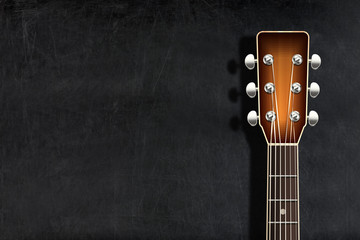 Head classical guitar against blank chalkboard or blackboard
