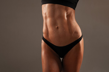 Sporty sexy girl with great abdominal muscles in black sportswear on black background. The pack abs on your stomach