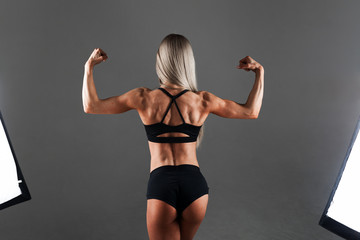 Strong Athletic woman Fitness Model posing back muscles, triceps, latissimus over black background. Studio Shooting