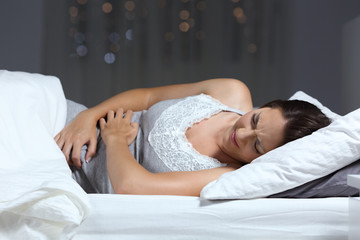 Woman suffering belly ache in the night on the bed
