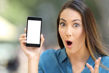 Amazed woman showing a blank smart phone screen