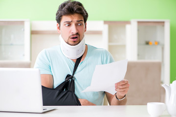 Young student man with neck and hand injury at home