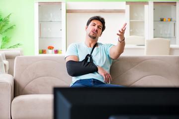 Arm injured man sitting on the sofa watching tv