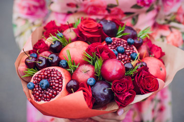 Bouquet flowers and fresh citrus fruits wrapped in coarse paper in hands