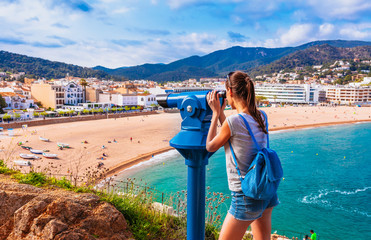Tourist woman in Badia bay in Tossa de Mar in Girona, Catalonia, Spain near of Barcelona. Ancient medieval castle with nice sand beach and clear blue water. Famous tourist destination in Costa Brava