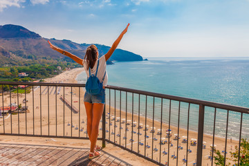 Young tourist woman on the beach and sea landscape with Sperlonga, Lazio, Italy. Scenic resort town village with nice sand beach and clear blue water. Famous tourist destination in Riviera de Ulisse