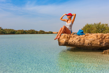 Tourist woman at the Red Sea coast and mangroves in the Ras Mohammed National Park. Famous travel destionation in desert. Sharm el Sheikh, Sinai Peninsula, Egypt.