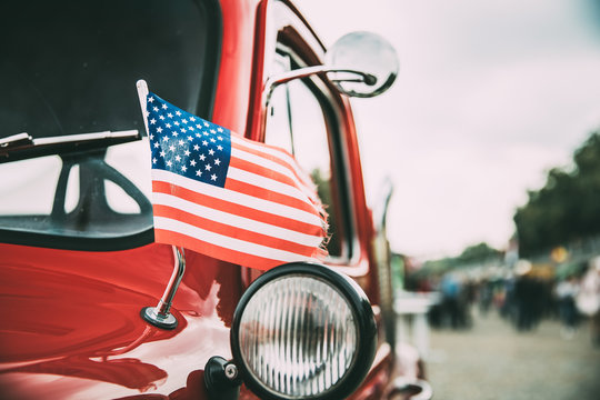 Close Side View Of Red Pickup Truck With Small American Flag Waving