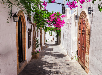 Zelfklevend Fotobehang Centraal Europa Narrow street in Lindos town on Rhodes island, Dodecanese, Greece. Beautiful scenic old ancient white houses with flowers. Famous tourist destination in South Europe