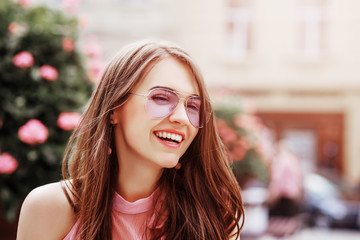 Outdoor close up portrait of young beautiful happy smiling woman wearing stylish pink aviator sunglasses posing in street of city. Copy, empty space for text