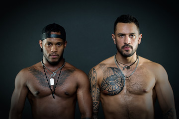 Fashion models with serious faces and fit bodies isolated on black background. Caucasian man with geometrical tattoos standing next to African guy with eagle tattoo on chest wearing cap backwards