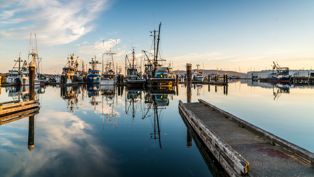 Bellingham, Washington / USA. 06. 17. 2018. Pond mirroning in the waters of the Pacific ocean with boats in the background.