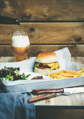 Classic burger dinner. Beef meat homemade burger with glass of lager beer, French fries and salad on white tray, rustic wooden wall at background, copy space