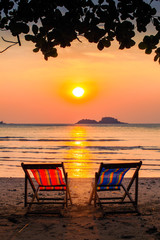 Loungers at the seaside at amazing sunset.