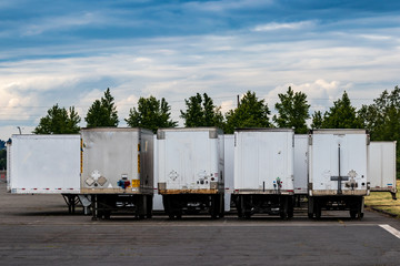 Semi tractor trailers parked in a row with doors closed under a blue cloudy sky