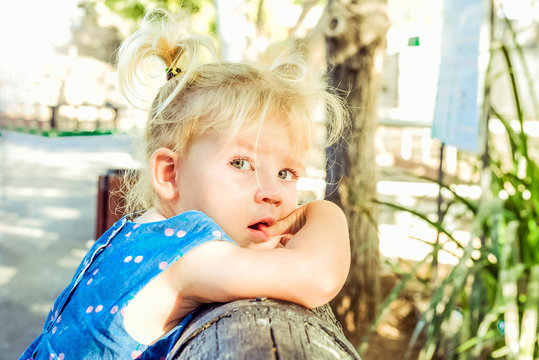 Close up portrait of bondy toddler girl with beautiful blue eyes with tears in the park. Child feelings and emothions concept. Seelctive focus, copy space.