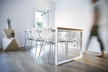 Stylish and modern scandinavian dining room with wooden table, design chairs and lamp. Beautiful space with white walls, wooden shapes and plants.