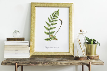 Modern room composition of wooden console with gold mock up poster frame, beautiful plant and letter in bottle. Stylish home interior.