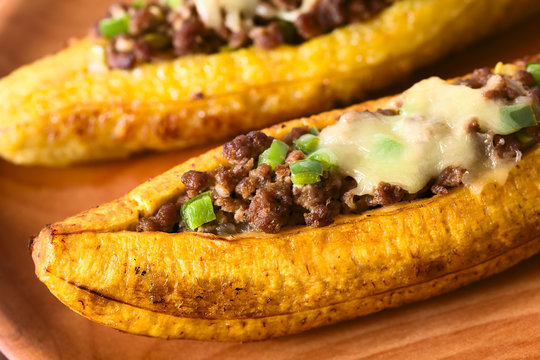 Baked ripe plantain stuffed with mincemeat, olive, green bell pepper, onion, traditional dish in Central America called Canoa de Platano (Plantain Canoe) (Selective Focus in the middle of the image)