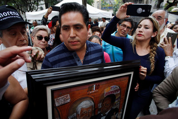 A supporter of Mexico's President-elect Andres Manuel Lopez Obrador holds a framed painting to give him as a present outside the campaign headquarters in Mexico City