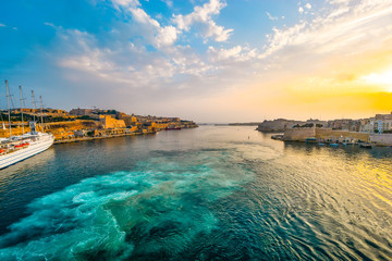 Sunrise at the Grand Harbour of Valletta Malta with sun hitting the old city and a small cruise ship