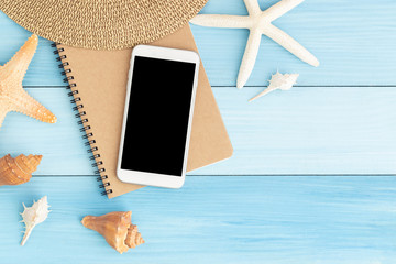 White smartphone on brown notebook on blue wooden floor,Flat lay photo of technology concept in summer