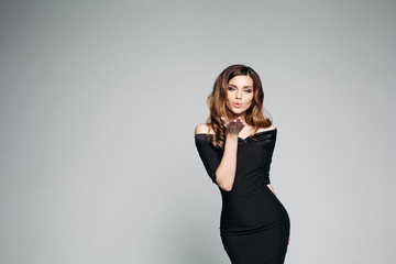Seductive brunette girl with perfect makeup and volumed hairstyle blowing air kiss by hand at camera. Sexy woman in black dress sending kiss, posing at grey studio background. Concept of fashion.