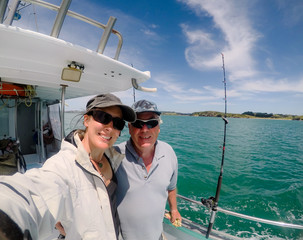 Selfie: father and daughter male and female tourists on fishing charter vessel in Far North District, Northland, New Zealand, NZ