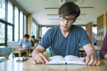 Smart confident young man studying late, he is sitting at desk and reading a book, knowledge and learning concept