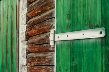 Painted white iron hinges on green wooden gates of shed close up. Textured detailed background with wood planks of barn is painted of vivid green paint with copy space. Rustic construction.