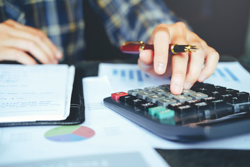 Businessman's hands with calculator at the office and Financial data analyzing counting