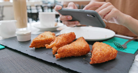 Woman taking photo on fried chicken wing