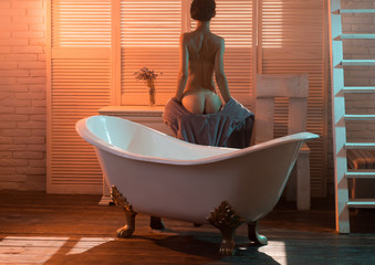 relax in bathroom in the morning. desire and seduction. naked woman going to take shower. Massage and spa salon concept. girl with sexy body relax in bath near tub.