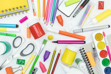 school supplies and stationary on white desk background. flat view