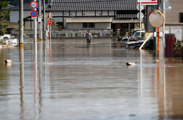 A local resident makes his way in a flooded area in Mabi town in Kurashiki