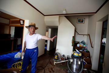 79-year-old local resident Isao Akutagawa, pauses as he tries to remove mud and debris from his house in a flood affected area in Mabi town in Kurashiki