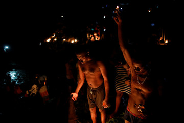 Pilgrims light candles during the celebration of the annual pilgrimage to the waterfall in Saut D'Eau