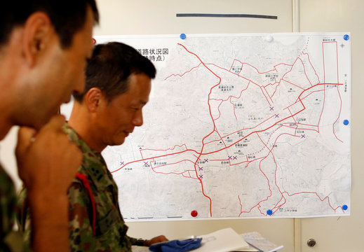 Japan Self-Defence Force soldiers walk past in front of a disaster map at disaster countermeasures headquarters at Kurashiki city government office in Kurashiki