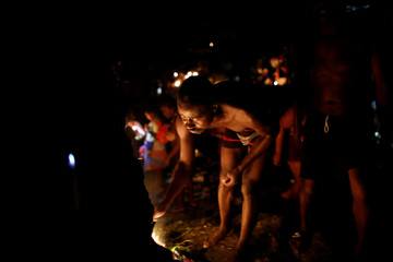 A pilgrim lights a candle during the celebration of the annual pilgrimage to the waterfall in Saut D'Eau