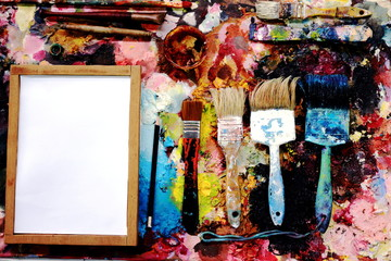 paint brushes and drawing paper on a color full painter in black ground.