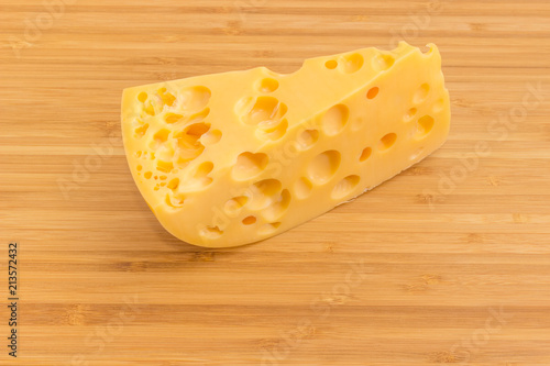 Piece Of Swiss Type Cheese On Bamboo Cutting Board Stock Photo And