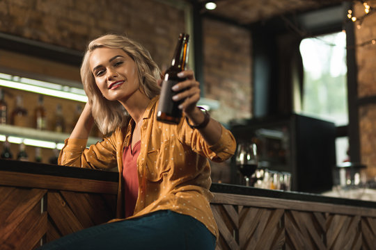 Have a drink. Pleasant blonde woman sitting at the bar counter and raising her beer bottle as if inviting to drink together with her