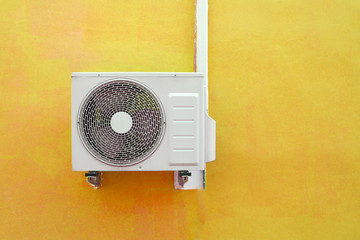 Air conditioning compressor near the yellow wall background